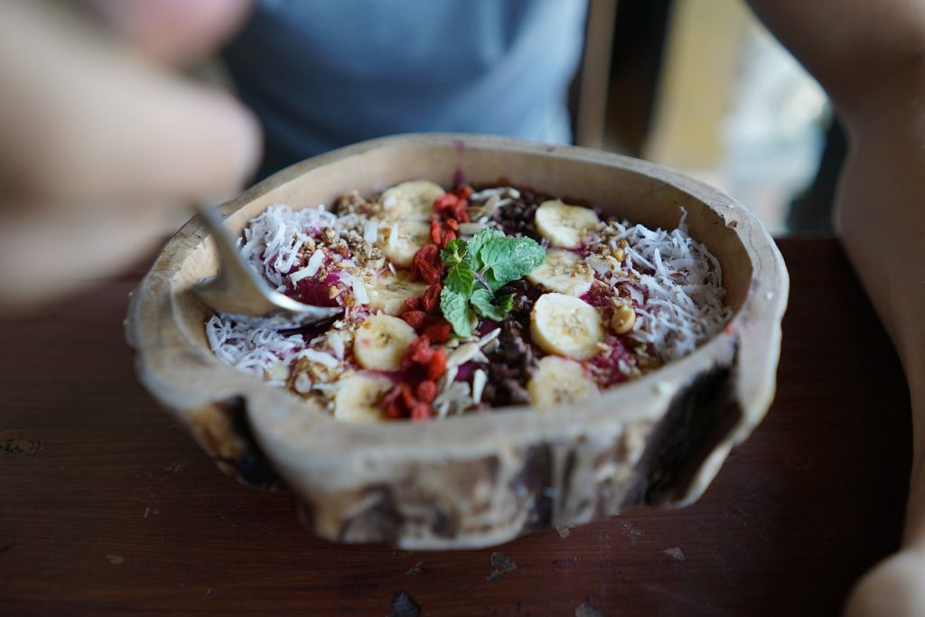 Styled açaí smoothie in a rustic bowl and topped with banana, coconut, seeds, and mint leaves